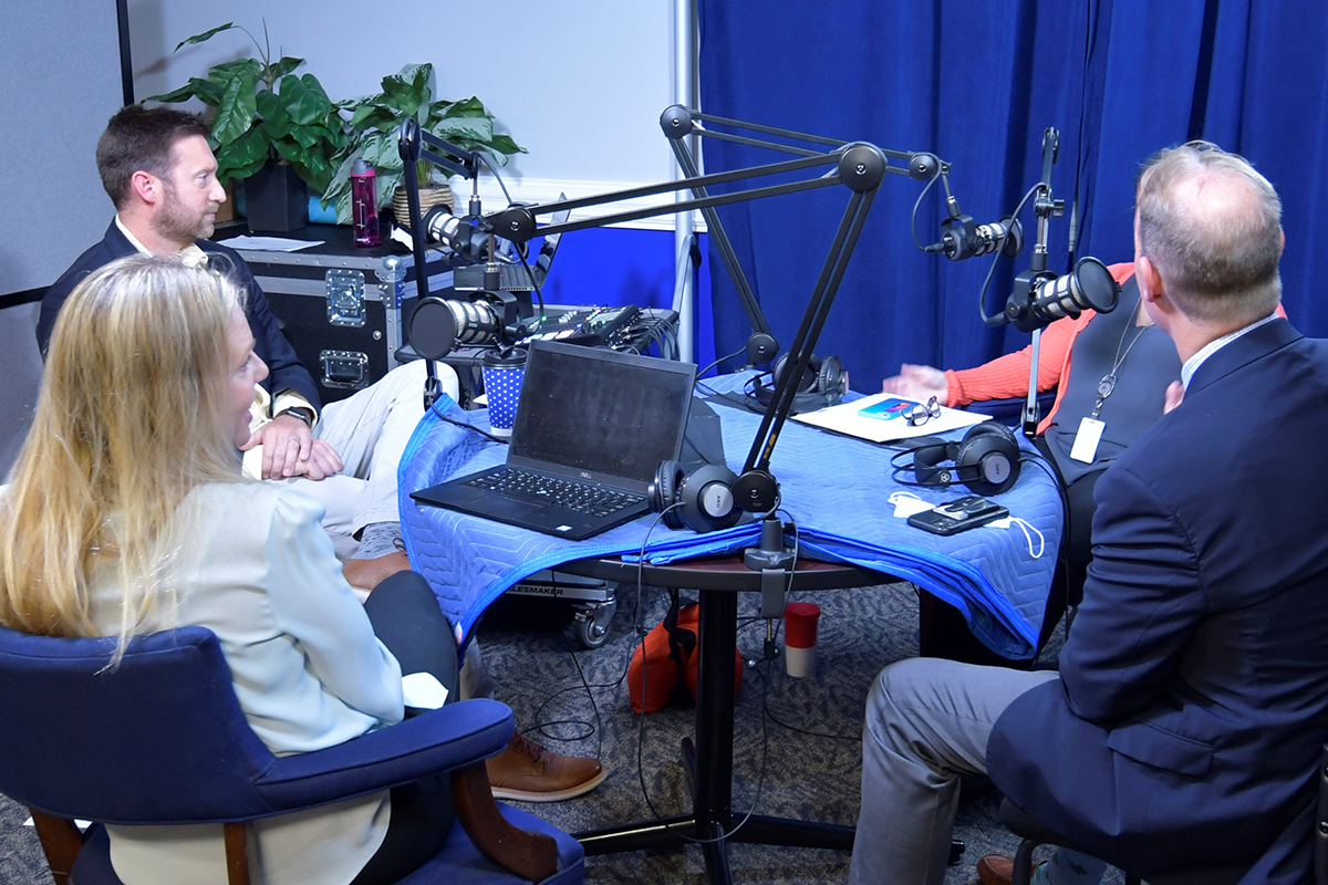 """Amelia Thorn speaks into a microphone with other guests on the """"All Things Judicial"""" podcast"""